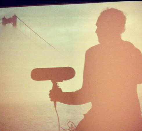 dreamy image of recordist holding microphone in front of the golden gate bridge